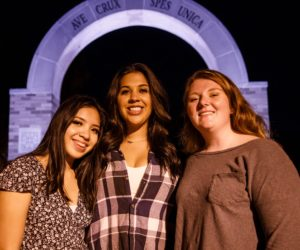 Three female students together at the arch from welcome weekend 2020.